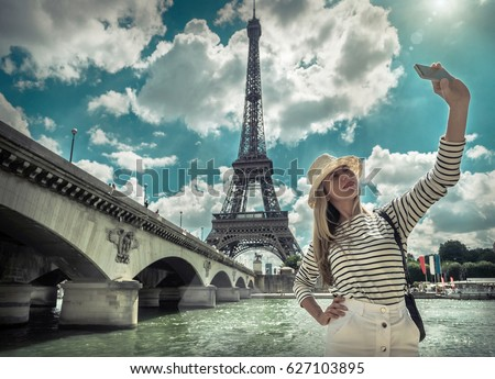 Woman tourist selfie near the Eiffel tower in Paris under sunlight and blue sky. Famous popular touristic place in the world. - Shutterstock ID 627103895