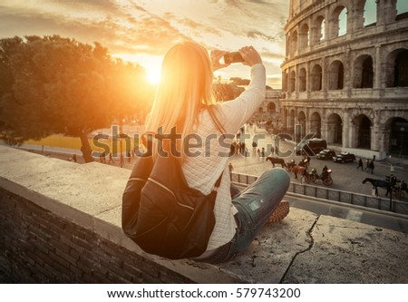 Woman tourist selfie with phone camera in hands near the Coliseum in Rome under sunlight and blue sky. Famous popular touristic place in the world. #579743200