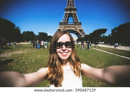 Woman tourist smiling and making travel selfie. Beautiful European girl enjoying vacation in Paris, France