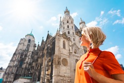 Woman tourist stands near St. Stephen's Cathedral on Stefansplatz in Vienna and enjoys the views of the main attractions of the city, Vienna, Austria