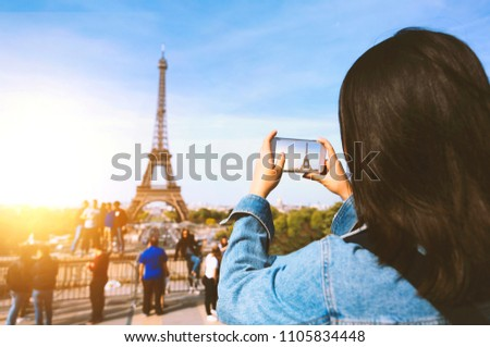 Woman tourist taking photo by phone near the Eiffel tower in Paris under sunlight and blue sky. Famous popular touristic place in the world. #1105834448