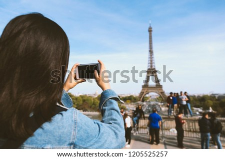 Woman tourist taking photo by phone near the Eiffel tower in Paris under sunlight and blue sky. Famous popular touristic place in the world. #1205525257
