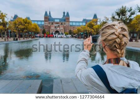 Woman tourist taking photo of the Rijksmuseum in Amsterdam on the mobile phone. Travel in Europe city trip concept