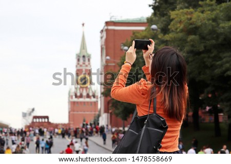 Woman tourist taking pictures of Moscow Kremlin on smartphone in summer. Crowd of tourists on the Red square, travel in Russia #1478558669