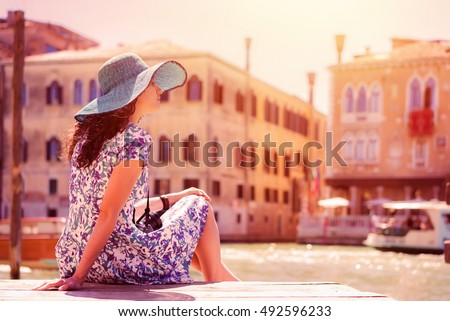 Woman tourist travel in Italy. Young lady with camera rest on an old street. Girl traveling to Venice.
