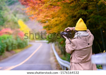 woman tourist traveler enjoy taking photo of the scenery Autumn view beside the road at Countryside, traveling in Countryside o Japan prefecture