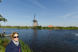 Woman tourist travelling in Holland in front of Dutch windmill, navy jacket, red bag, blue sky and beautiful weather
