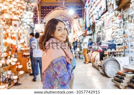 Woman tourist walking among countless shops in Grand Bazaar market in Istanbul. Shopping and travel in Turkey concept