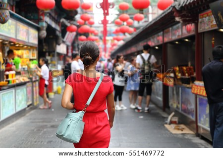 Woman tourist walking in chinatown on china travel. Asian girl on Wangfujing food street during Asia summer vacation. Traditional Beijing snacks being sold at chinese chinatown outdoor market. #551469772