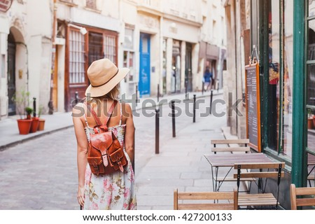 woman tourist walking on the street, summer fashion style, travel to Europe