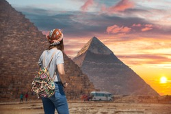 Woman tourist walks on the background of the pyramids in Giza. Egypt