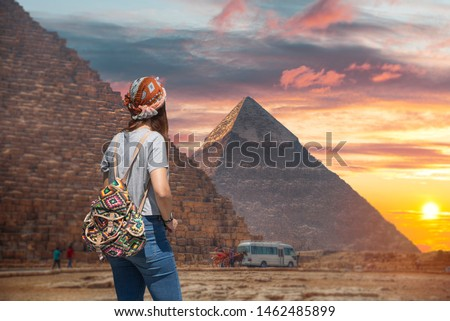 Woman tourist walks on the background of the pyramids in Giza. Egypt Stock photo ©