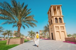 Woman tourist wearing a maroon turban and yellow backpack walks along old wind towers and palms in Bur Dubai and Creek district. Travel and sightseeing spots