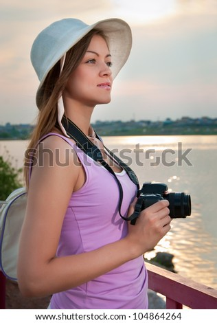 woman tourist with a camera standing near the rails