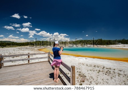 Woman tourist with camera overlooking hot thermal spring Sunset Lake in Yellowstone National Park, Black Sand Basin area, Wyoming, USA