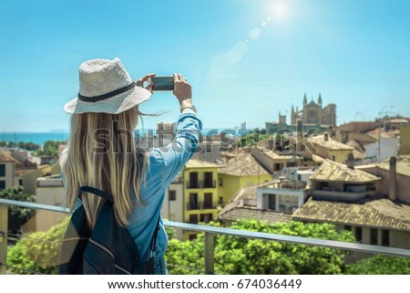 Woman tourist with her phone camera in hands shooting in Palma de Mallorca under sunlight and blue sky in sunny day. One of popular touristic place in Palme de Mallorca. #674036449