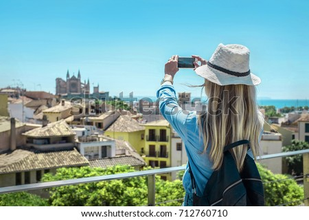 Woman tourist with her phone camera in hands shooting in Palma de Mallorca under sunlight and blue sky in sunny day. One of popular touristic place in Palme de Mallorca. #712760710