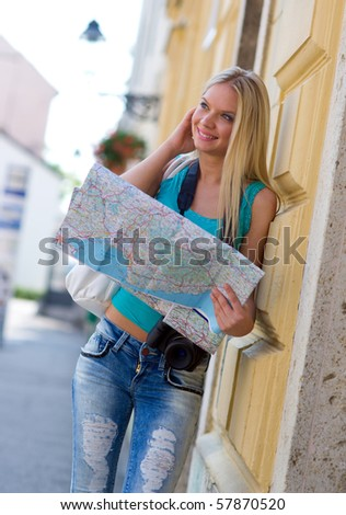 woman tourist with map and camera next to wall