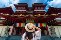 Woman toursit is traveling at Buddha relic temple with Singapore urban city skyline with beautiful landmark and iconic view. (Chinese means Buddha relic temple)