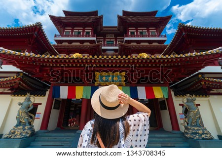 Woman toursit is traveling at Buddha relic temple with Singapore urban city skyline with beautiful landmark and iconic view. (Chinese means Buddha relic temple) Zdjęcia stock ©