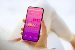 Woman tracking periods by using menstrual calendar app on phone