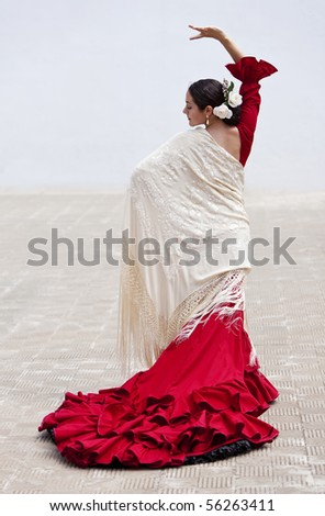 Woman traditional Spanish Flamenco dancer dancing outside in a red dress with a cream colored shawl
