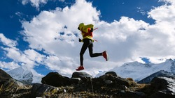 Woman trail runner cross country running in high altitude winter nature