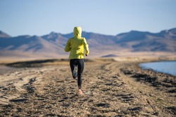 Woman trail runner cross country running on winter high altitude lakeside