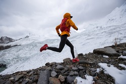 Woman trail runner cross country running to winter mountain top