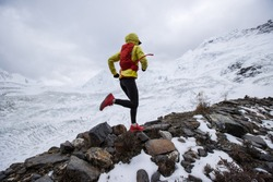 Woman trail runner cross country running up hill to winter snow mountain top