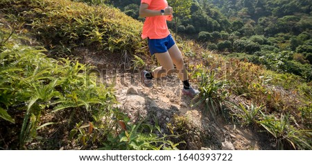 Woman trail runner running downhill on mountain slope in tropical forest Stockfoto ©