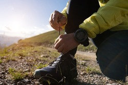 Woman trail runner tying shoelace while cross country running  on mountain top