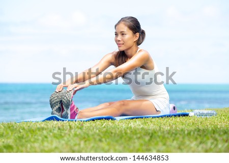 Woman training fitness stretching legs exercise outside by the ocean sea Beautiful fit female fitness girl model sitting on grass doing stretch exercising after workout Mixed race Asian female model