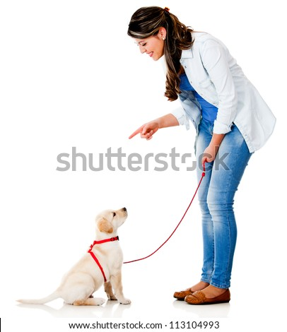 Woman training her dog - isolated over a white background