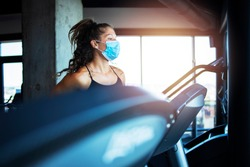 Woman training in gym during covid-19 pandemic and coronavirus. Sportswoman running on treadmill and wearing hygienic face mask to protect herself against highly contagious corona virus.