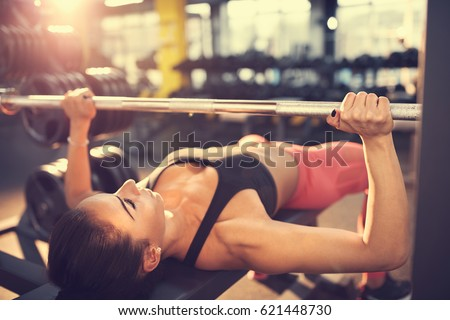 Woman training on bench press #621448730