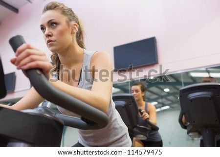Woman training on exercise bike in a spinning class in gym
