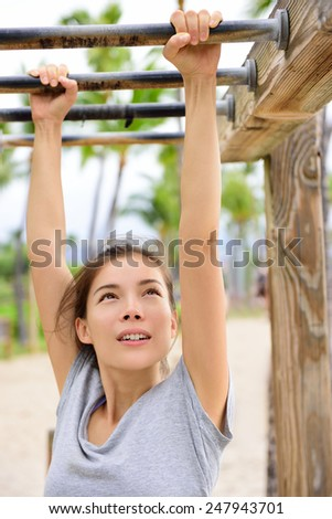 Woman training on fitness brachiation ladder or monkey bars hanging swinging from rung to rung as part of crossfit workout routine. Beautiful Asian girl doing toning exercises exercising arms.