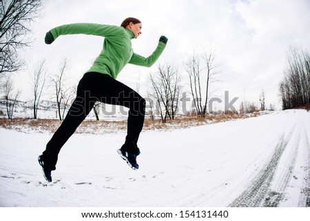 Woman training running in winter on snow. Copy space. Health and fitness concept.