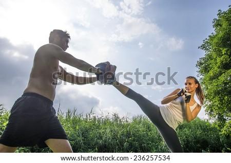 Woman training  self defense martial arts with coach - Martial arts athlete kicks