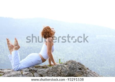 woman training yoga on beauty landscape - stock photo