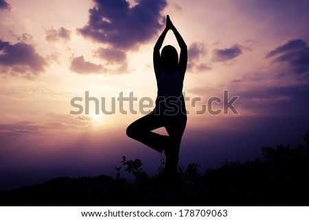 Woman training yoga on the mountain at sunset