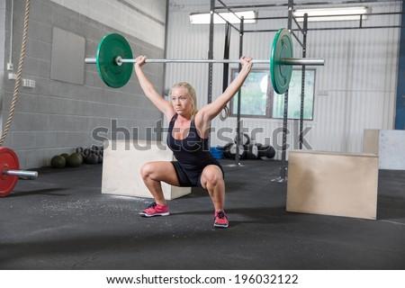 Woman trains squats at crossfit center