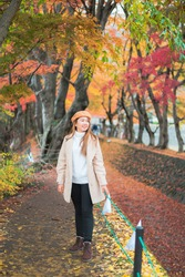 Woman travel in Japan., autumn season portrait of young Asian beautiful woman in park of japan.  beauty fashion concept at Japan.