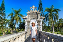 Woman traveler at Karangasem Taman Ujung, Water Palace on Bali, Indonesia in a sunny day