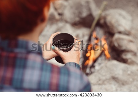 Woman traveler hands holding cup of tea near the fire outdoors. Adventure, travel, tourism and camping concept. Hiker drinking tea from mug at camp. Coffee cooked over a campfire on the nature.