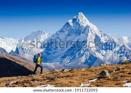Woman Traveler hiking in Himalaya mountains with mount Everest, Earth's highest mountain. Travel sport lifestyle concept. Ama Dablam mountain view