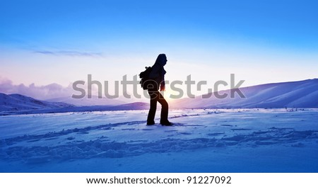Woman traveler hiking in winter mountains, trekking in wintertime cold snowy weather, girl silhouette over natural blue sky with bright sunset and beautiful landscape, freedom concept