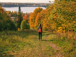 Woman traveler hiking with backpack at autumn hill. Travel Lifestyle concept adventure vacations outdoor.
