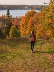 Woman traveler hiking with backpack at autumn hill. Travel Lifestyle concept adventure vacations outdoor. Vertical view.